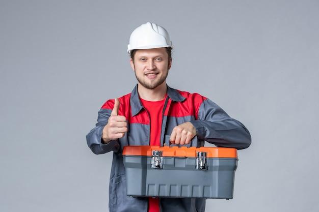 Vista frontal, construtor masculino de uniforme e capa de ferramentas segurando o capacete em fundo cinza