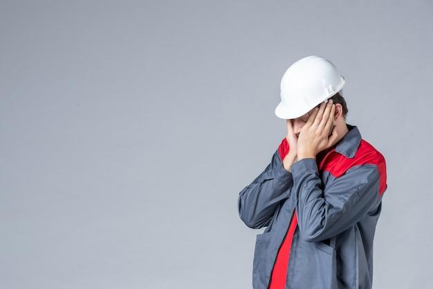 Vista frontal, construtor masculino de uniforme e capacete estressado em fundo cinza