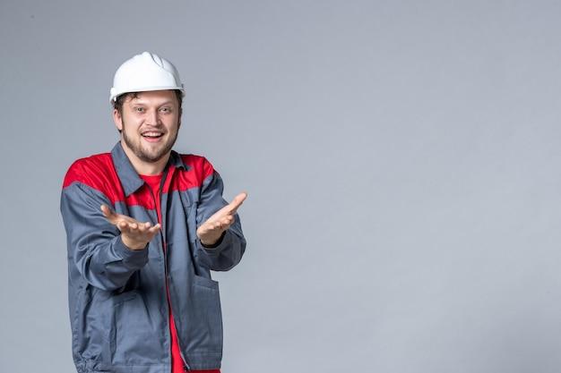 Vista frontal, construtor masculino de uniforme em fundo claro
