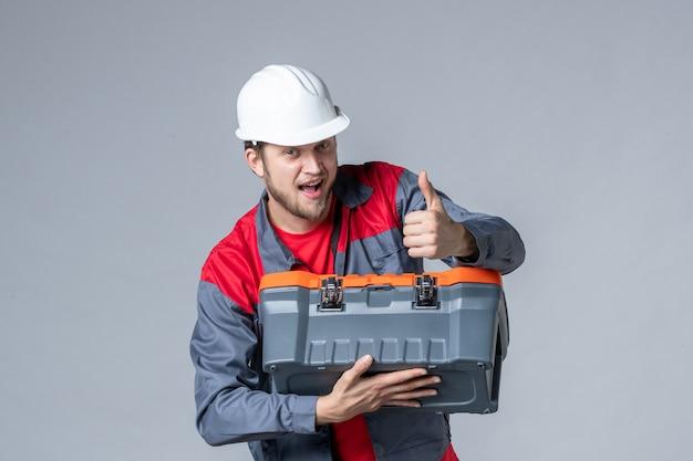 Vista frontal, construtor masculino de uniforme tentando abrir a maleta de ferramentas em fundo cinza