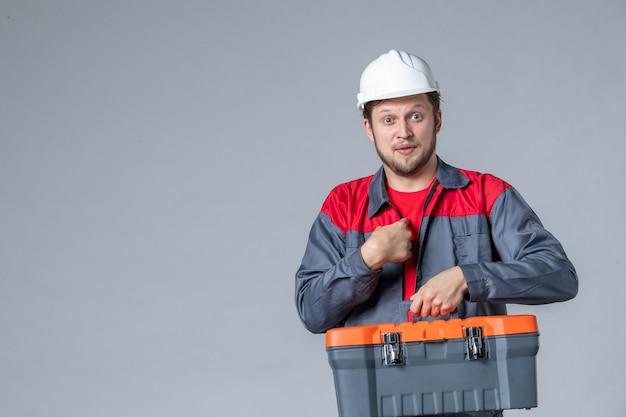 Vista frontal, construtor masculino em uniforme segurando a maleta de ferramentas em fundo cinza