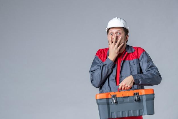 Vista frontal, construtor masculino uniformizado segurando a caixa de ferramentas surpreso e animado com um fundo cinza