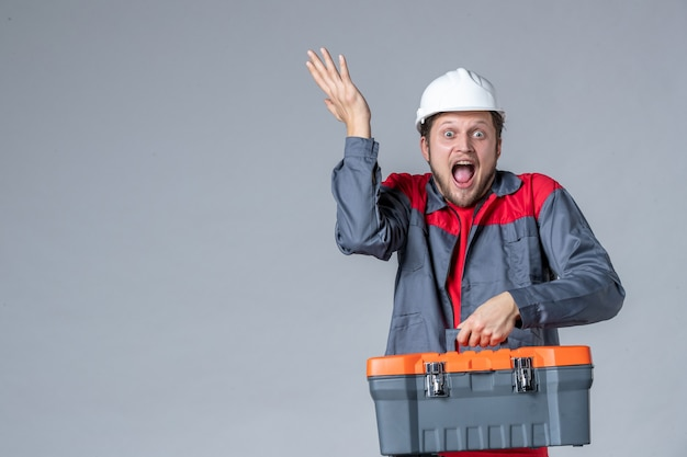 Vista frontal, construtor masculino uniformizado segurando a maleta de ferramentas com rosto animado em fundo cinza