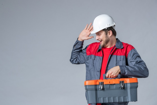 Vista frontal, construtor masculino uniformizado, segurando a maleta de ferramentas e rindo no fundo cinza