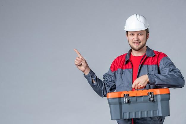 Vista frontal, construtor masculino uniformizado segurando uma caixa de ferramentas pesada em fundo cinza
