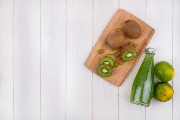 Vista frontal, cópia espaço kiwi em uma tábua com tangerinas verdes e uma garrafa de suco em uma parede branca