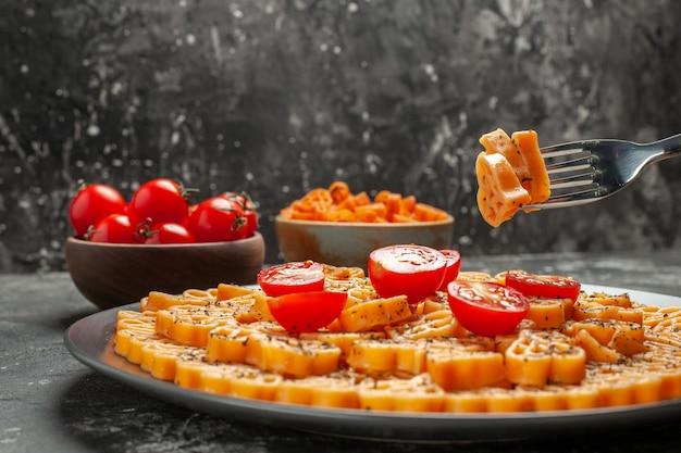 Vista frontal, corações de macarrão italiano cortam tomate cereja em prato oval garfo tomate cereja e macarrão coração vermelho em tigelas na mesa escura