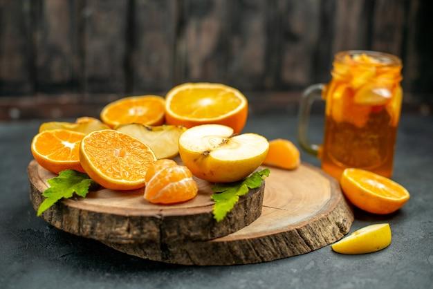 Vista frontal cortando maçãs e laranjas na placa de madeira coquetel no escuro