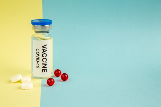 Vista frontal covid- vacina com pílulas vermelhas sobre fundo amarelo-azul cor pandêmica laboratório de saúde covid- vírus hospital ciência droga espaço livre