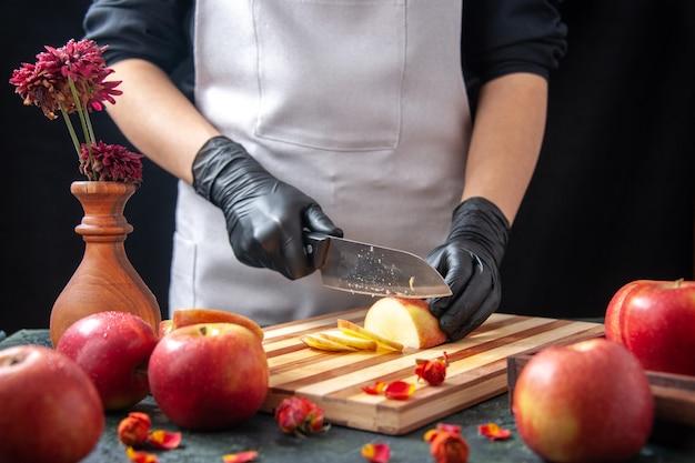Vista frontal cozinheira cortando maçãs em vegetais escuros dieta salada refeição bebida exótica fruta