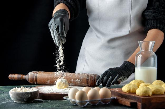 Vista frontal cozinheira desenrolando a massa e despejando farinha no escuro cozinha forno hotcake massa assar bolo torta trabalhador ovo