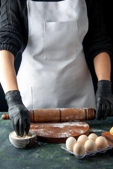 Vista frontal cozinheira esticando a massa com farinha no escuro cozinha hotcake massa crua assar bolo trabalhador torta