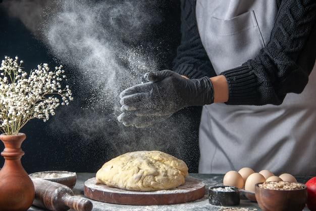 Vista frontal cozinheira esticando a massa com farinha no escuro trabalho massa crua padaria torta forno pastelaria hotcake