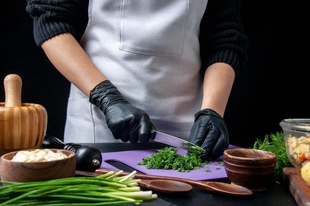 Vista frontal cozinheira fazendo salada de vegetais corte verdes em fundo escuro cozinha feriado trabalho comida refeição trabalho cor cozinha