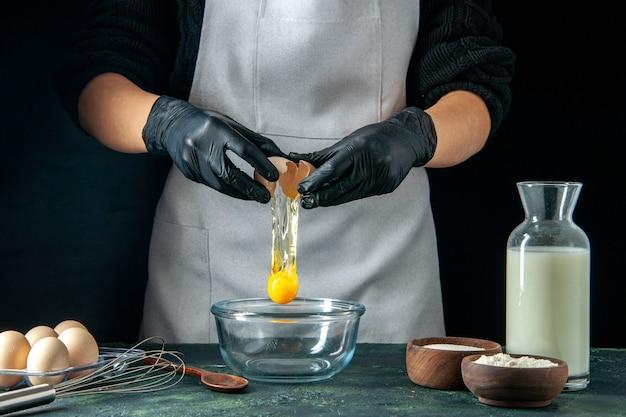 Vista frontal cozinheira partindo ovos para massa no escuro trabalho de pastelaria tortas de bolo padaria trabalhador cozinha