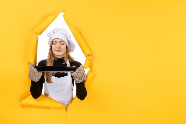 Vista frontal cozinheira segurando a panela preta no sol amarelo tempo comida foto trabalho cozinha emoção cozinha cor
