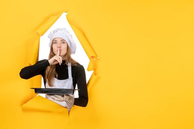 Vista frontal cozinheira segurando uma panela preta com biscoitos no amarelo foto emoção sol comida cozinha cozinha cores trabalho