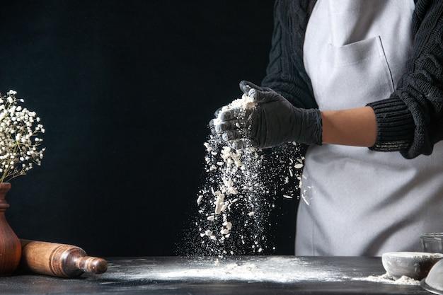 Vista frontal cozinheira servindo farinha na mesa para a massa na massa escura ovo cozinha trabalho padaria bolo quente cozinha