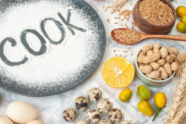 Vista frontal cozinheiro escrito farinha com cereais ovos sementes nozes e geleia no fundo branco torta comida asse leite cozinhando geléia fruta bolo cor