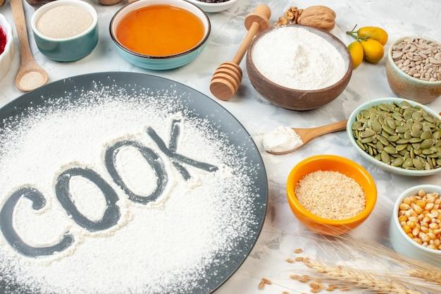 Vista frontal cozinheiro escrito farinha com ovos, cereais, sementes, nozes e geleia no fundo branco torta comida assar cozinhando geléia frutas bolo cor