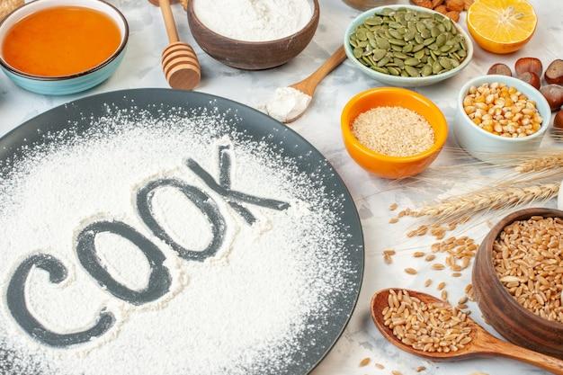 Vista frontal cozinheiro escrito farinha com ovos, cereais, sementes, nozes e geleia no fundo branco torta de comida assar leite cozinhar geléia