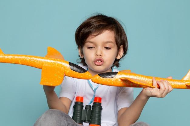 Vista frontal criança menino fofo adorável brincando com aviões de brinquedo laranja no azul