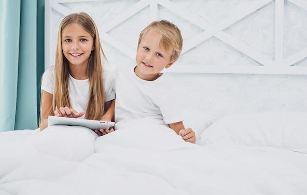 Vista frontal crianças ficando na cama enquanto estiver jogando em um tablet