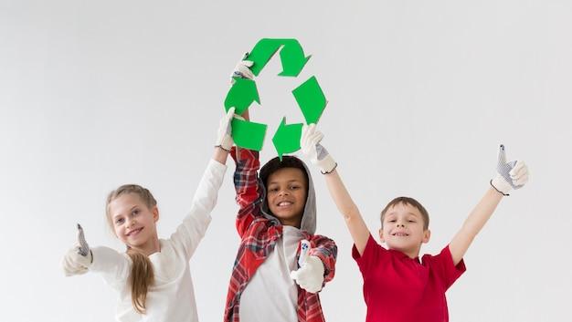 Vista frontal, crianças jovens, segurando, sinal reciclar