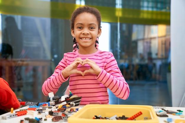 Vista frontal da adorável garota africana sorridente em pé, olhando para a câmera e fazendo coração com as mãos.