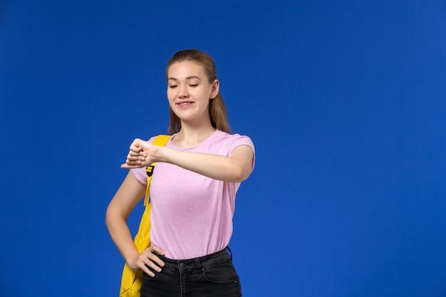 Vista frontal da aluna com camiseta rosa e mochila amarela olhando para o pulso na parede azul