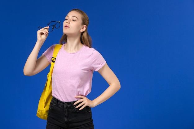 Vista frontal da aluna com camiseta rosa e mochila amarela segurando óculos de sol na parede azul claro