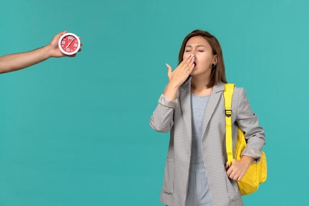 Vista frontal da aluna com jaqueta cinza e mochila amarela, bocejando na parede azul clara
