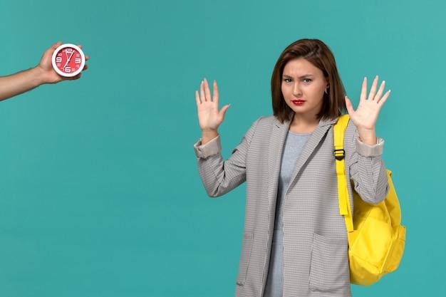 Vista frontal da aluna com jaqueta cinza e mochila amarela na parede azul clara