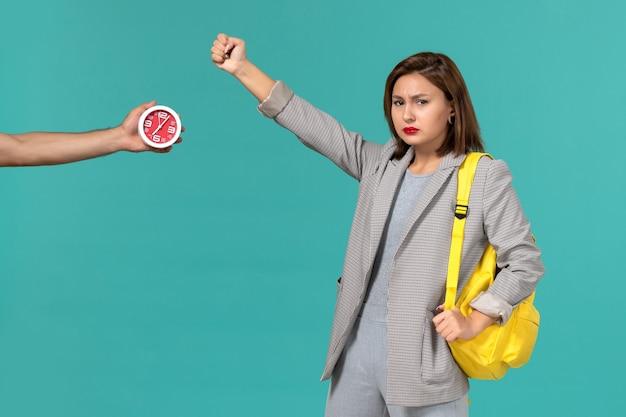 Vista frontal da aluna com jaqueta cinza e mochila amarela, posando na parede azul claro