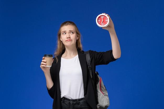 Vista frontal da aluna com uma jaqueta preta usando uma mochila segurando relógios e café na parede azul-clara.
