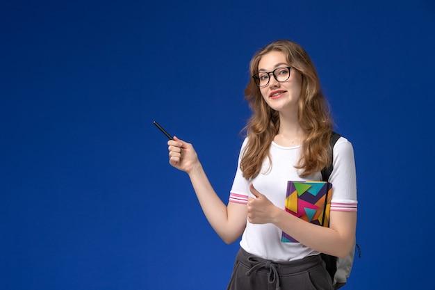 Vista frontal da aluna de camisa branca segurando uma caneta e o caderno na mesa azul