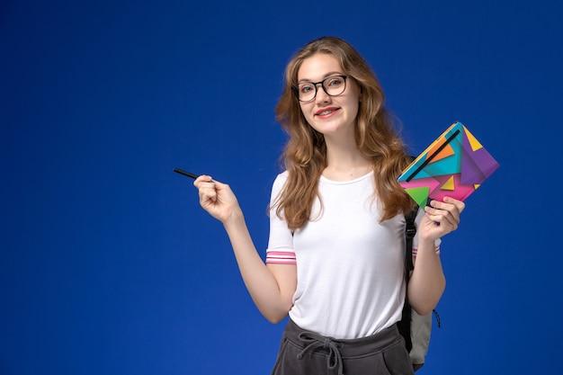 Vista frontal da aluna de camisa branca segurando uma caneta e um caderno na parede azul