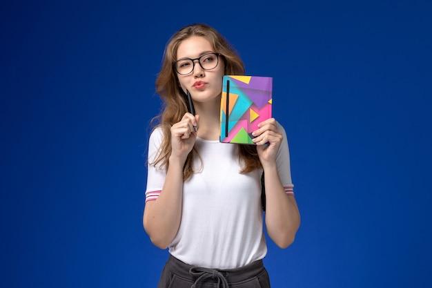 Vista frontal da aluna de camisa branca segurando uma caneta e um caderno pensando na parede azul