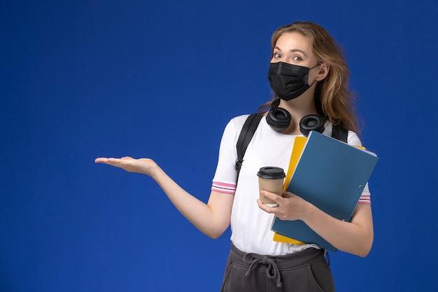 Vista frontal da aluna de camisa branca, usando uma máscara estéril preta de mochila, segurando café e arquivos na parede azul