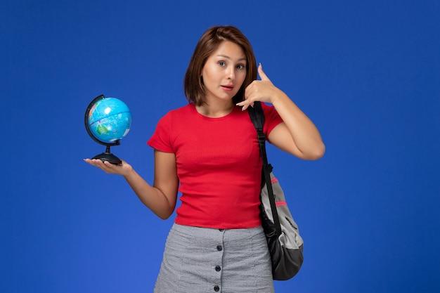Vista frontal da aluna de camisa vermelha com mochila segurando o globo, posando na parede azul