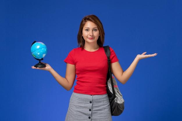 Vista frontal da aluna de camisa vermelha com mochila segurando o globo, sorrindo na parede azul