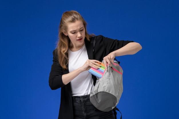 Vista frontal da aluna de jaqueta preta segurando uma mochila cinza e o caderno, colocando-o dentro da parede azul.