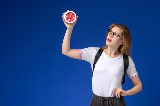Vista frontal da aluna em camisa branca com mochila segurando relógios na parede azul