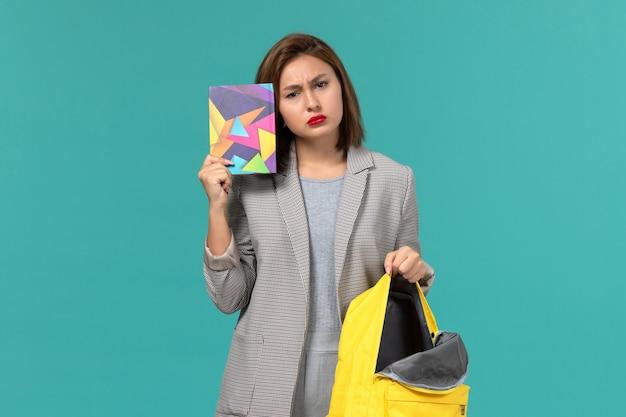 Vista frontal da aluna em jaqueta cinza segurando uma mochila amarela e um caderno na parede azul clara