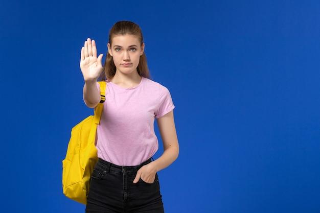 Vista frontal da aluna em uma camiseta rosa com mochila amarela mostrando o sinal de pare na parede azul