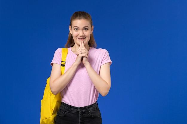 Vista frontal da aluna em uma camiseta rosa com mochila amarela, parada na parede azul