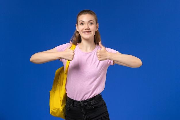 Vista frontal da aluna em uma camiseta rosa com mochila amarela posando e sorrindo na parede azul