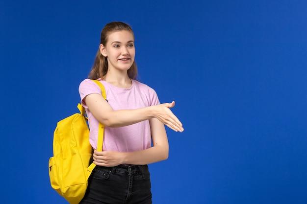 Vista frontal da aluna em uma camiseta rosa com mochila amarela sorrindo e apertando a mão na parede azul