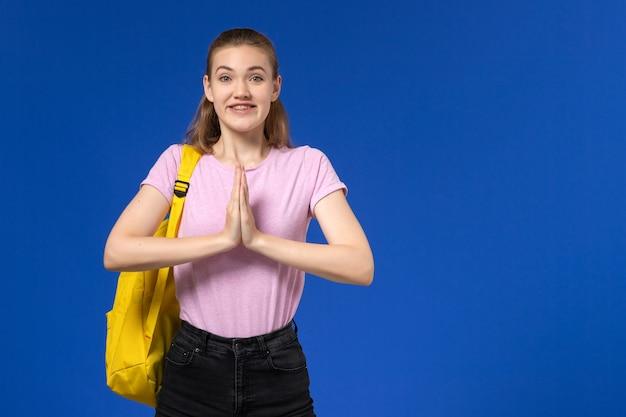 Vista frontal da aluna em uma camiseta rosa com mochila amarela sorrindo na parede azul clara