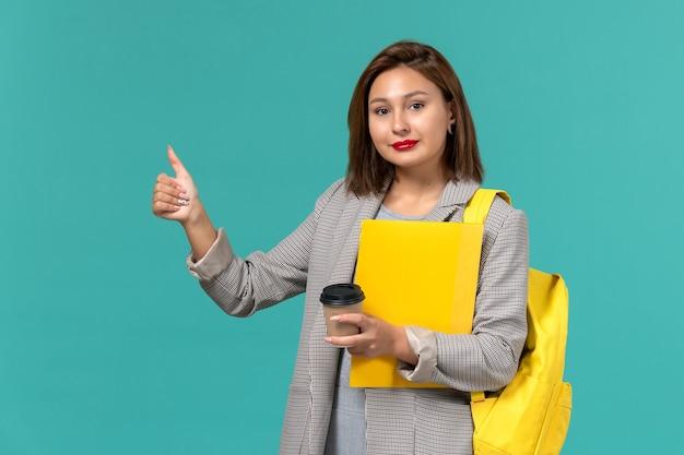 Vista frontal da aluna em uma jaqueta cinza com sua mochila amarela segurando arquivos e café na parede azul clara